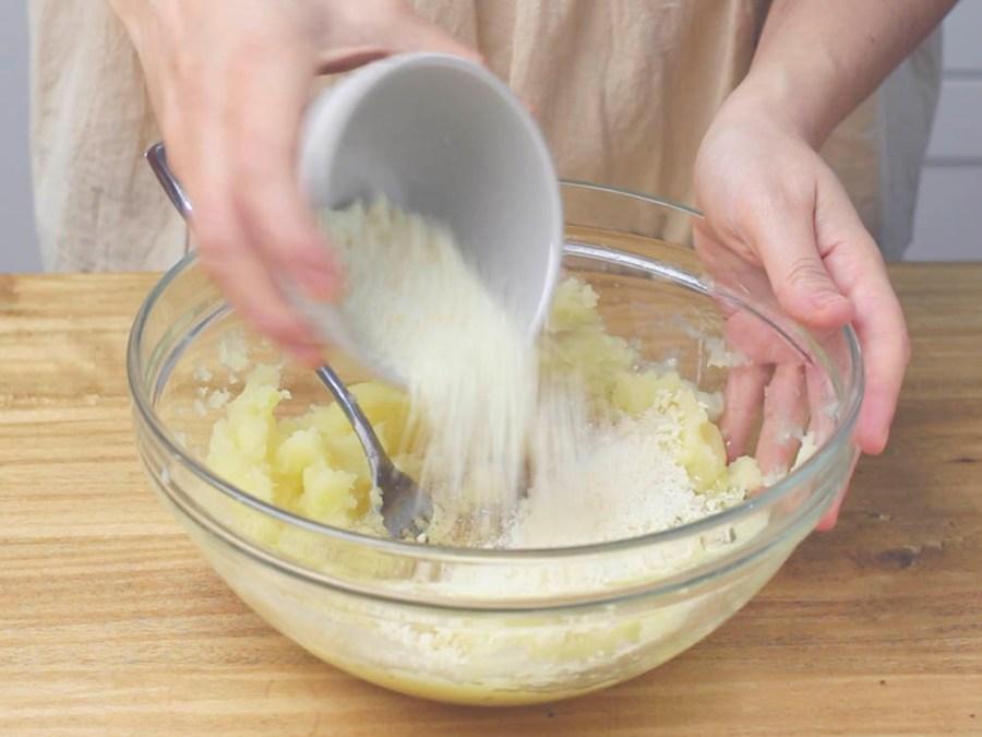 Aggiungiamo alle patate 50 gr di formaggio grattugiato, il sale a piacere, l'uovo, il pepe bianco e la farina di riso. Mescoliamo bene tutti gli ingredienti.