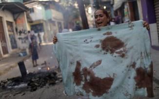 Moradora da Mangueira protesta mostrando toalha suja de sangue após mortes na comunidade (Foto: Foto/REUTERS/Ricardo Moraes )