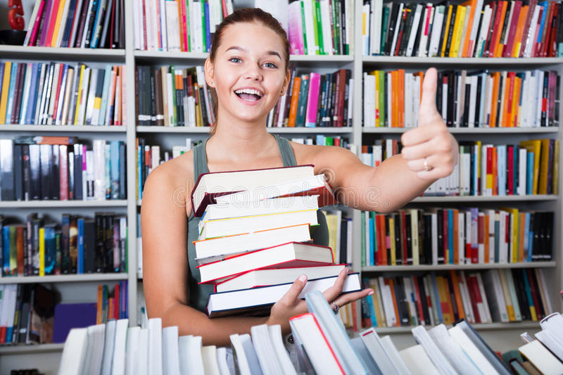 girl-holding-stack-books-shows-thump-up-bookstore-ordinary-84963273