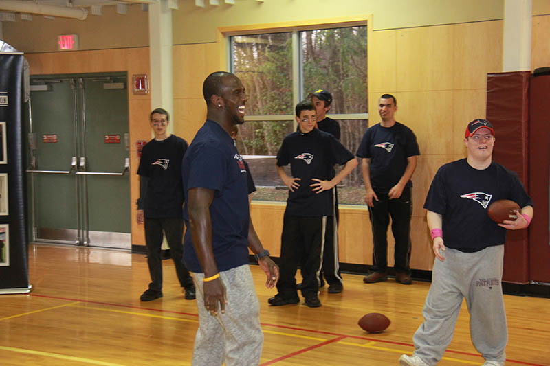 Patriots safety Devin McCourty laughs with Foxborough resident Mike McCarthy, right, during a flag football event inside the gymnasium of the Invensys Foxboro branch of the Hockomock Area YMCA.