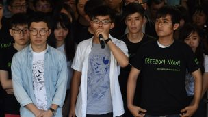 Joshua Wong, centre, with fellow Umbrella Movement leaders Nathan Law, left, and Alex Chow, addresses the assembled media before their sentencing on August 17. Photo: Anthony Wallace/AFP