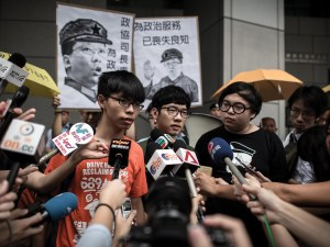 Bailed democracy activists Joshua Wong (C) and Nathan Law (L) speak to the press after their arrival at the Court of Final Appeal for the first hearing in their bid to appeal their jail sentences in Hong Kong on November 7, 2017.