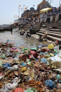 Indian scavengers look for coins and other valuable items from among the offerings of devotees in the Ganges at Varanasi