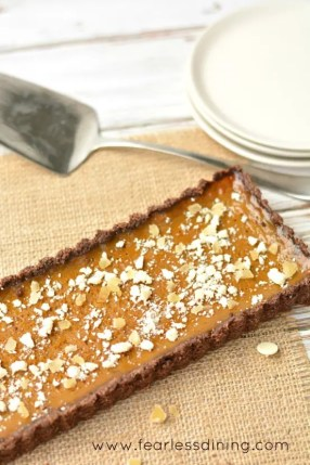 Gluten free pumpkin tart with white chocolate, candied ginger, and dark rum. The tart is on a table with a serving utensil and plates next to it.