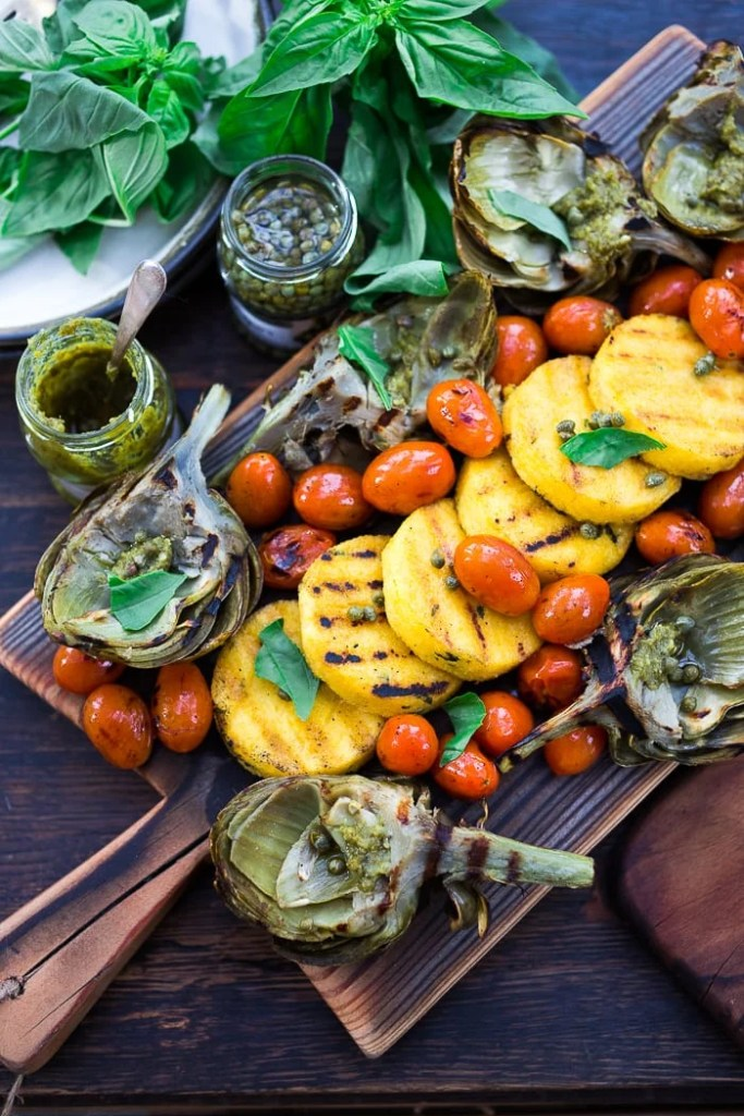 Grilled Artichokes and Polenta with Blistered tomatoes, pesto, capers and fresh basil-- served family style ...perfect for a casual summer evening! Vegan and GF | www.feastingathome.com| #grilledartichokes
