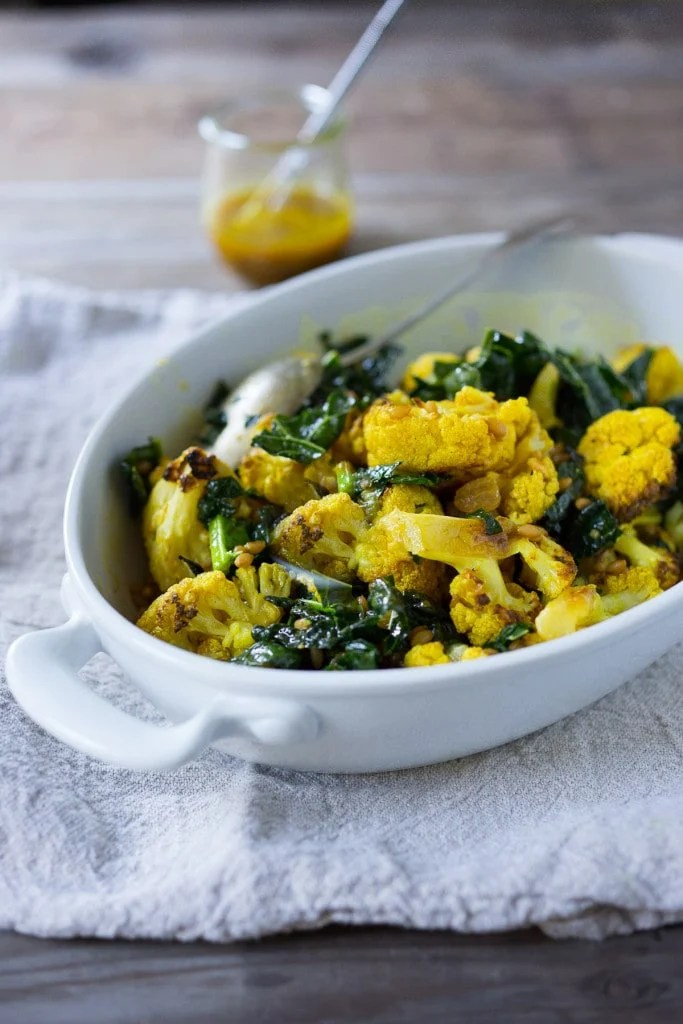 Roasted Cauliflower Salad with farro (or any cooked grain), lacinato kale and an earthy turmeric dressing. Delicious and healthy, it can be a served warm as a fall side dish, or chilled as a salad| www.feastingathom.com