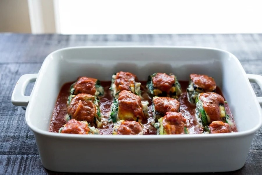 Zucchini Rolls with Spinach and Basil, baked in marinara sauce and topped with optional smoked mozzarella.| www.feastingathome.com
