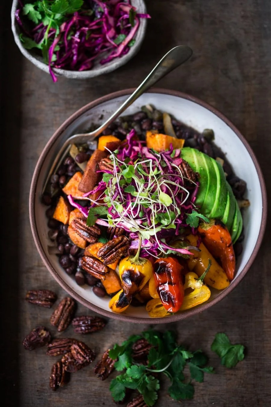 Vegan Mexican-style, Oaxacan Bowl with roasted chipotle sweet potatoes and sweet peppers over a bed of warm seasoned black beans. Topped with a crunchy cabbage slaw, avocado and toasted Chipotle Maple Pecans. | www.feastingathome.com
