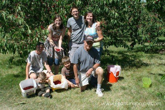 Extended family picking cherries