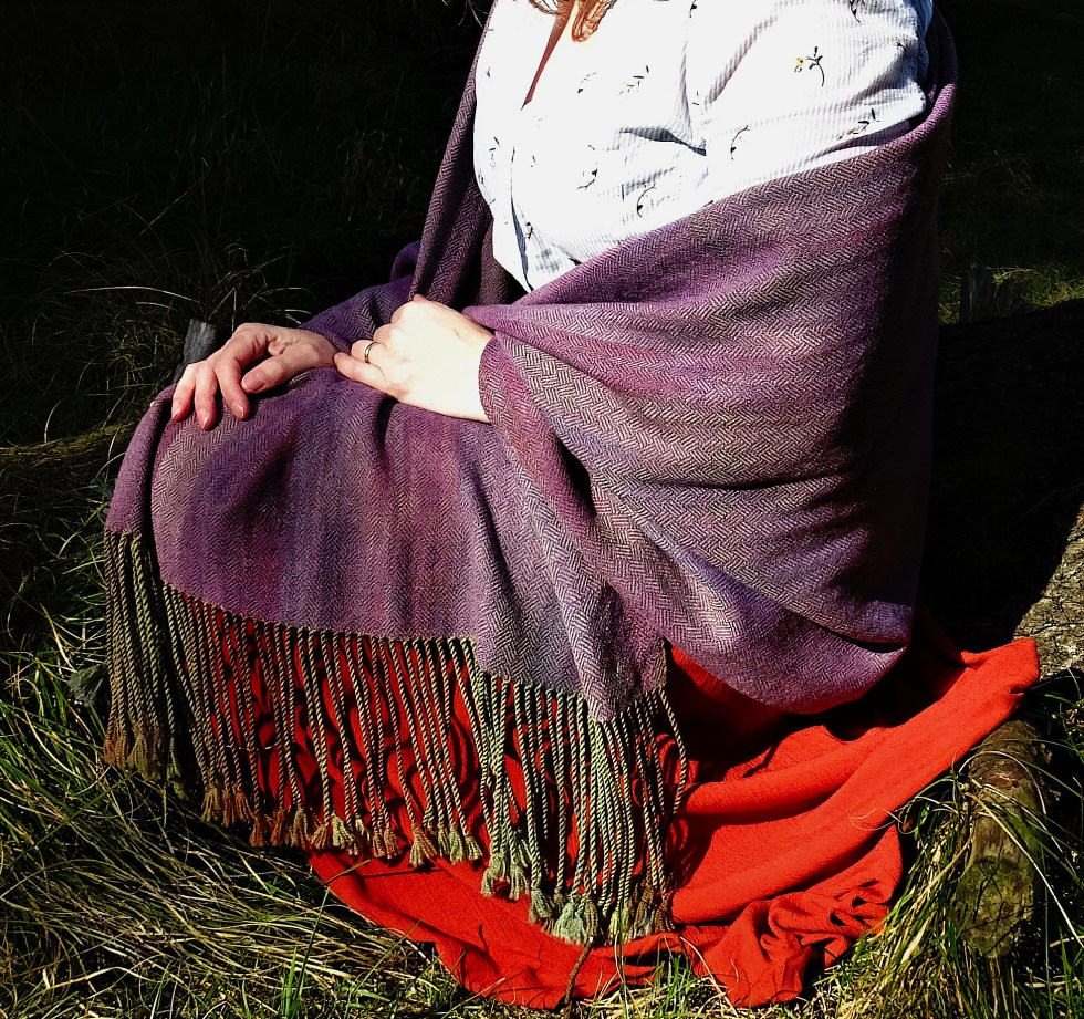 a purple shawl against a blue shirt and red skirt