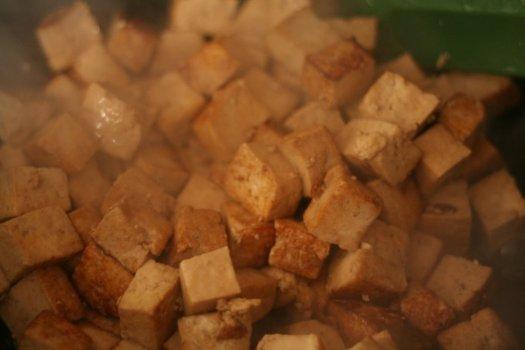 Stir-frying tofu up close