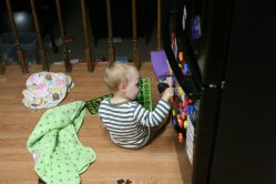 Spencer putting his new number and letter magnets on the fridge
