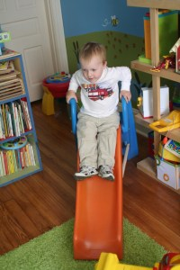 Spencer sliding in the toy room at the Comisars'