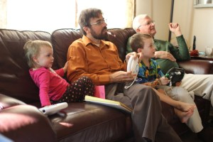 Rob and Spencer play monster truck Wii while Meg and Grandpa Felty watch