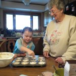 Meg putting the blueberries in the muffins