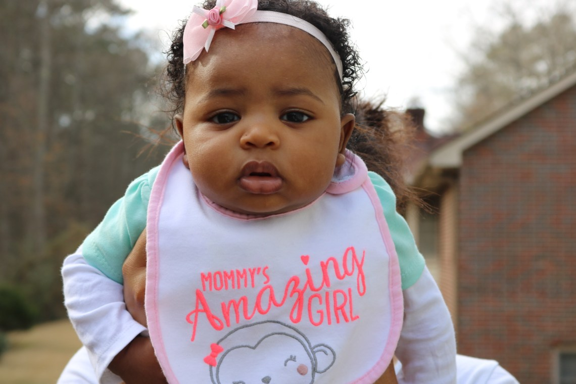baby girl African American with pink bow and wearing a bib that says mommy's amazing girl