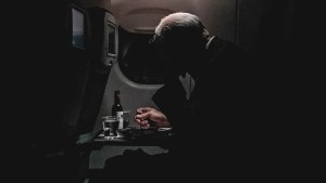 Man on a plane drinking alcohol