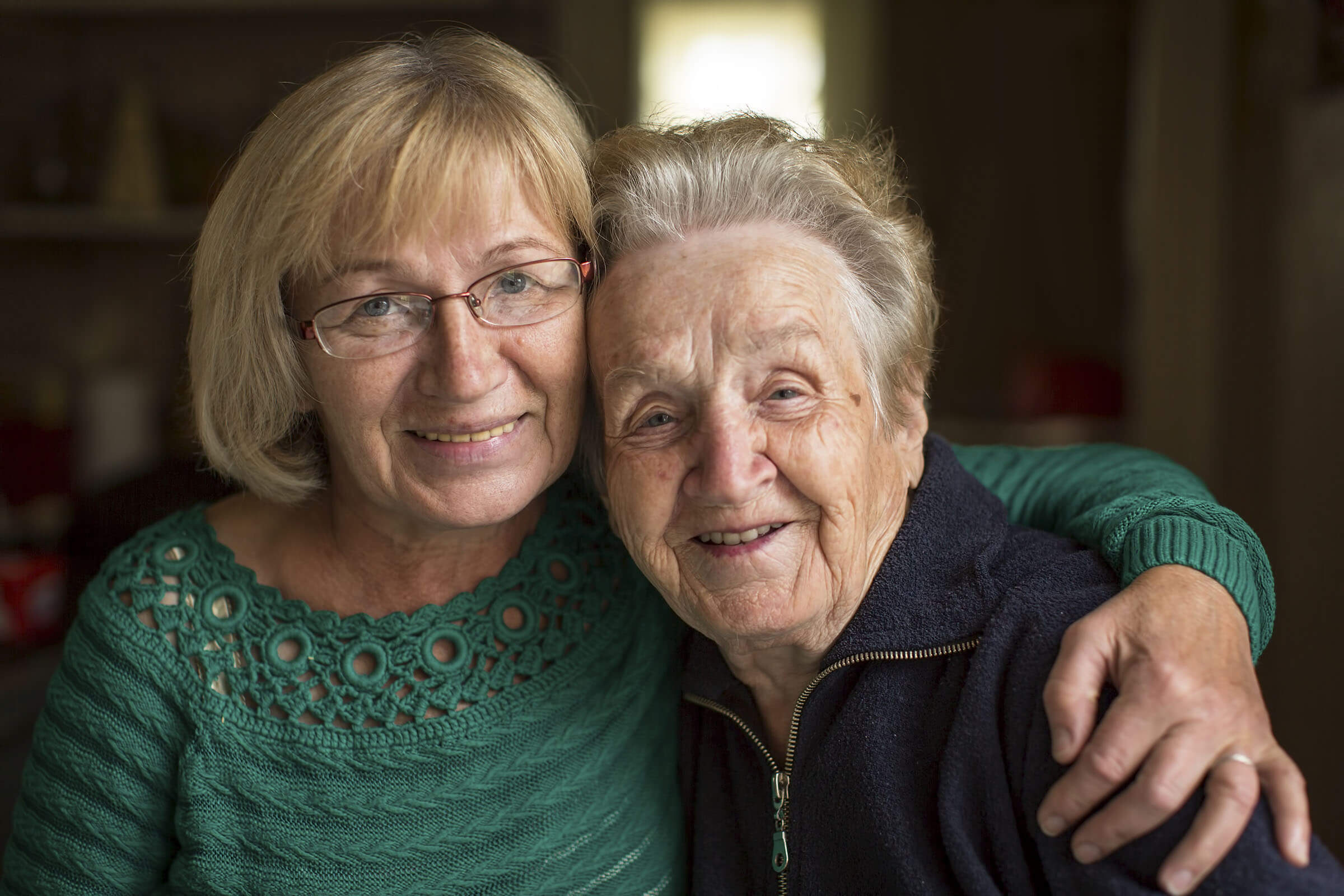 Two older women embracing one another
