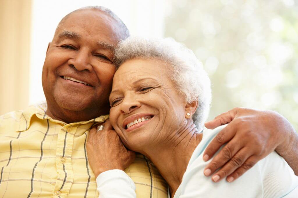 Older couple sitting together and embracing one another
