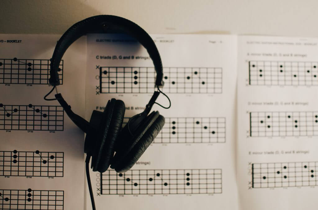 Black headphones sitting on a sheet of music