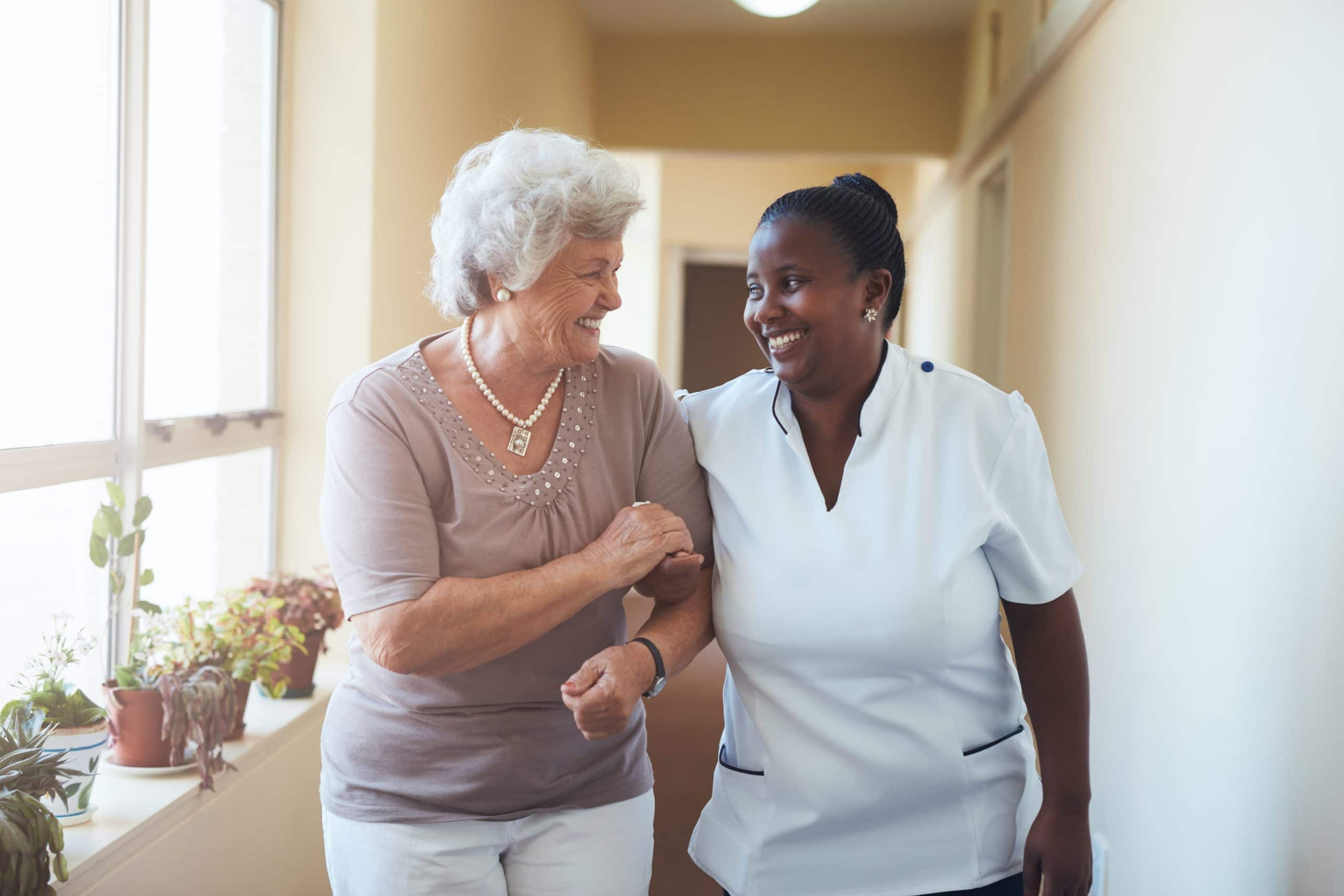 Smiling home caregiver and senior woman walking together through a corridor