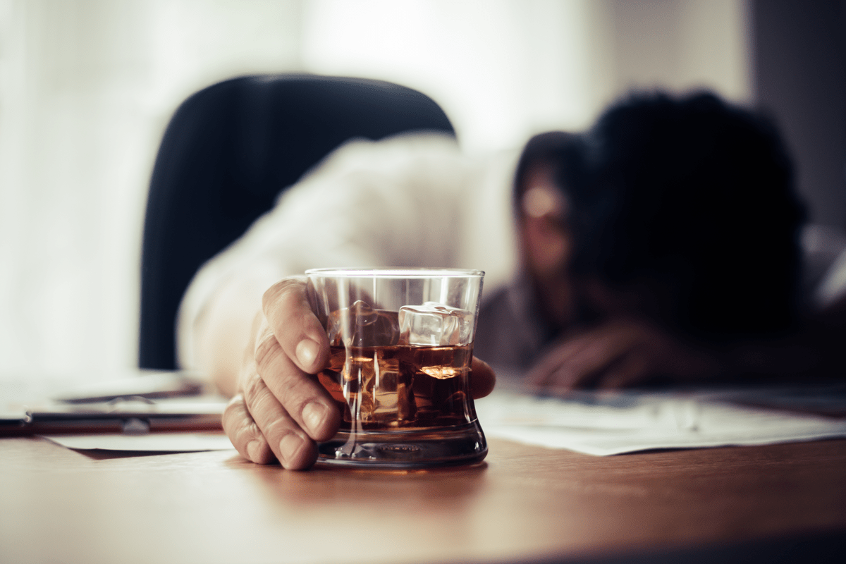 Adult laying their head on a table while holding an alcoholic drink