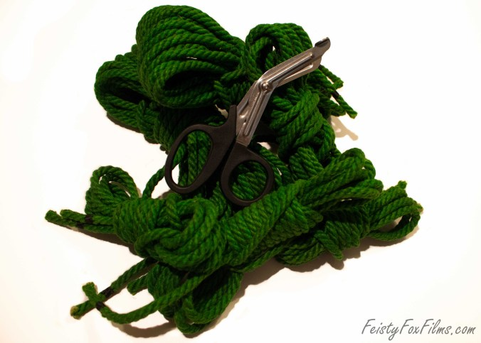 Six piles of bundles up green bondage rope, of various lengths, lie in a heap on the ground with black-handled safety scissors sitting on top of the pile.