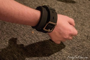 Taylor's right arm is extended, palm facing away from the camera. They are wearing Stockroom's thick silicone bondage cuff tightly around their wrist.