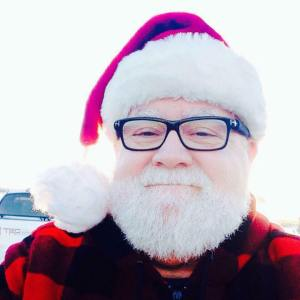 An exceptionally adorable older man with a pure white beard and mustache poses outdoors by the water. He is wearing dark glasses, a Santa hat, and a red and black oversized plaid coat, and he looks just like Santa. He is smiling with both his mouth and his eyes, and looks like someone who is laid-back and happy the majority of the time.