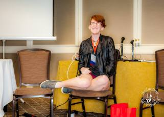 Taylor sits on a dining chair holding a microphone and grinning widely. Their legs are tucked underneath them, legs sticking out the side, and they're wearing sneakers, short red shorts, a fitted black tank top, and a worn black leather jacket. Their hair is swooping to one side and they're wearing a Woodhull name badge.