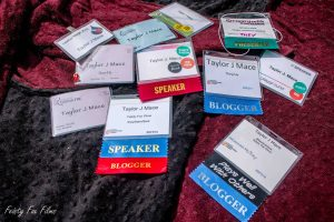A pile of 11 conference badges spanning from 2016-2018. Some are marked as a presenter, others are not.