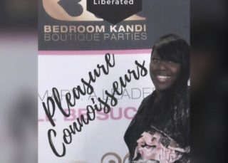 "Shelly stands in front of a floor to ceiling sigh that says ""Bedroom Kandi boutique parties, stimulated, educated, liberated, Pleasure Connoisseurs"". Her body is facing sideways and she is looking at the camera and smiling really big. She is Blackk, her hair is straight, pulled over the shoulder that is facing the camera and she has side bangs. She is wearing all black and holding a bundle of something white and pink that you can't make out in her arm."