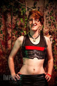 Taylor stands with their hands on their hips, grinning at the camera. They're wearing a micro-crop top made of mesh with a horizontal red stripe, pleather pants, and a bike tube chest harness with metal gears and chains on the front.