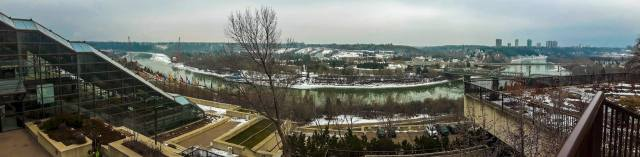 panorama of a riverfront. it's winter and there is snow everywhere, the river partly iced over. the greens, blues, and teals in the water and overcast sky are very vibrant. in the forefront of the image there are some buildings, steps, and little planters. there are bridges crossing the river at each end