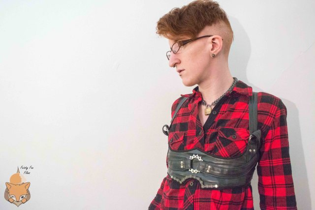 Taylor is wearing a red and black button up shirt, over which they've got a bike tube chest harness with metal gears and chains on the front.