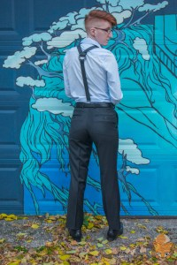 Taylor stands facing a garage door with some sort of blue and green painting on it. They're wearing a light blue button-up shirt, black dress pants, and black bike tube suspenders with a metal gear in the center. Their hair is shaved on the sides and back, a bit longer on the top.