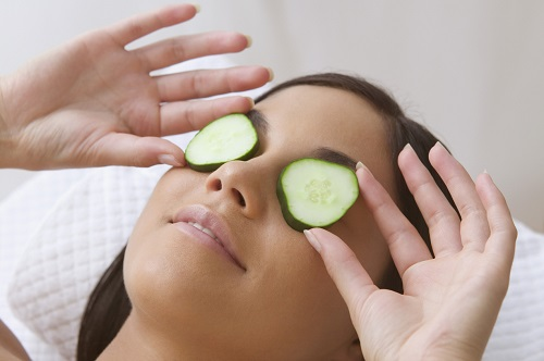 Young woman resting with cucumbers on her eyes