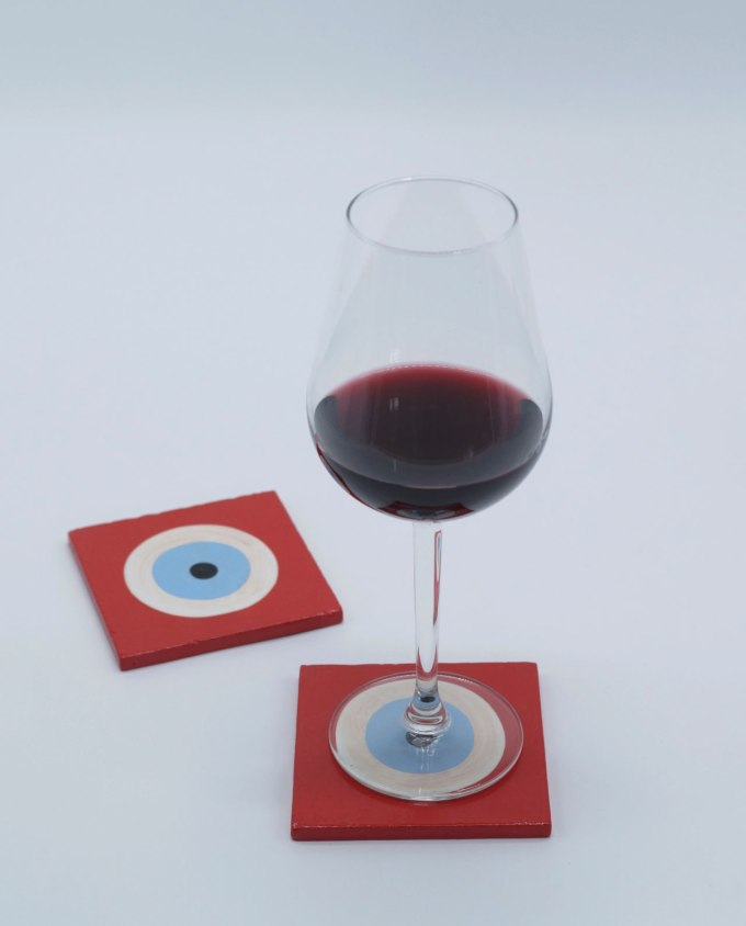 A handmade wooden red evil eye coaster
