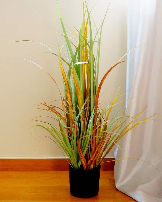 An artificial plant of green-orange leaves in pot to decorate your space, for indoors.