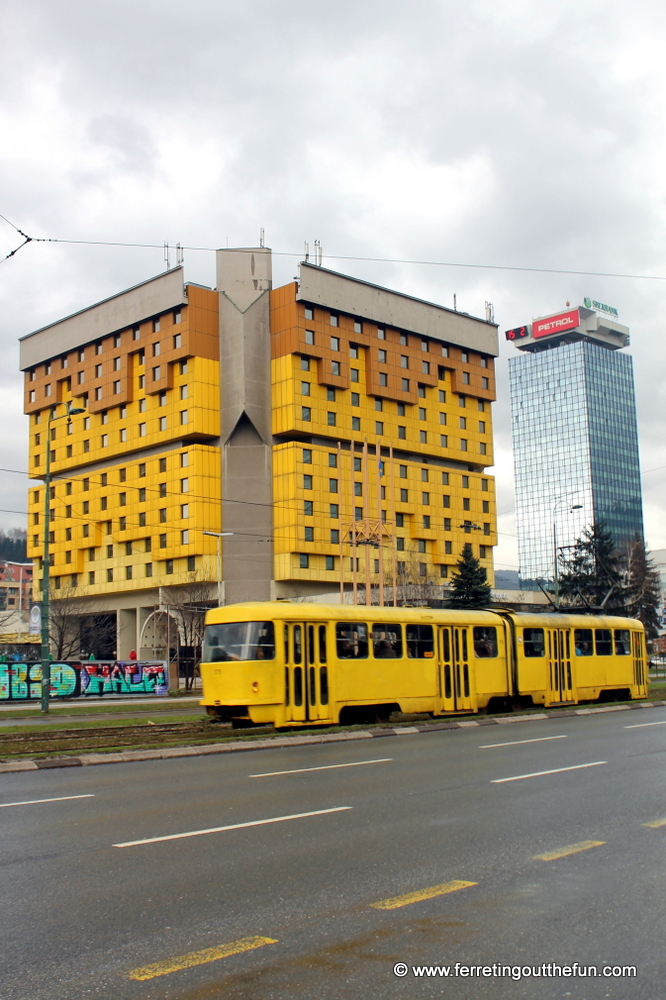A yellow tram glides by the restored Holiday Inn on Sniper Alley in Sarajevo