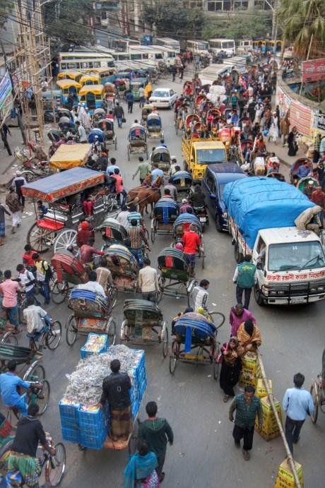 Die meisten Transportmodi im öV Dhakas in einem Bild: Zu-Fuß-Gehen, Fahrradrickshaw, Pferdekutsche im Linienverkehr (ja, wirklich!), CNG, Pick-up, Bus