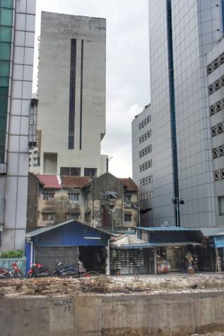 Welch ein Kontrast: ein von Hochhäusern umzingeltes älteres Haus in Johor Bahru. Übrigens: Singapur mit seiner vorbildlichen Stadtentwicklung liegt gerade mal 1 Kilometer Luftlinie entfernt