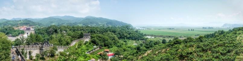 Ein Stück der Great Wall führt entlang der chinesisch-nordkoreanischen Grenze, die hier auf dem Gewässer im rechten Teil des Bildes verläuft