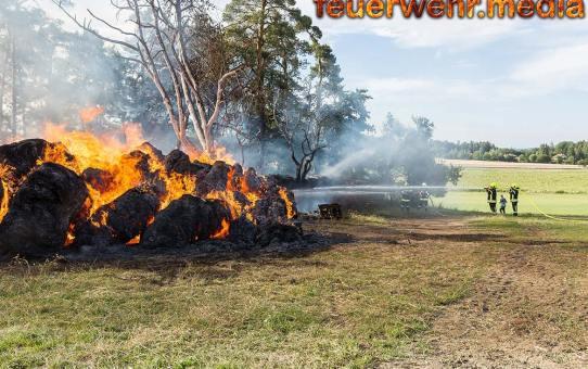 Brand von Strohrundballen und Brennholzlager droht sich auf Wald auszubreiten