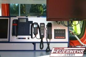 Bilck auf den vorderen Funkarbeitsplatz mit einem Digital- und einem Analogfunkgerät sowie einem Telefon.