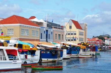 Pastel-painted waterside warehouses and boats on Curacao Waterfront