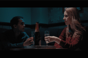 Characters from Immortality a man and a woman drinking champagne at a small table in a bar..