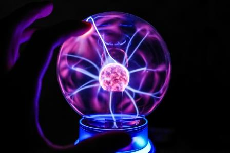 A blue and purple plasma lamp in a clear globe on black ground