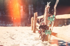 Snowboards and skis against a fence in a snowy field