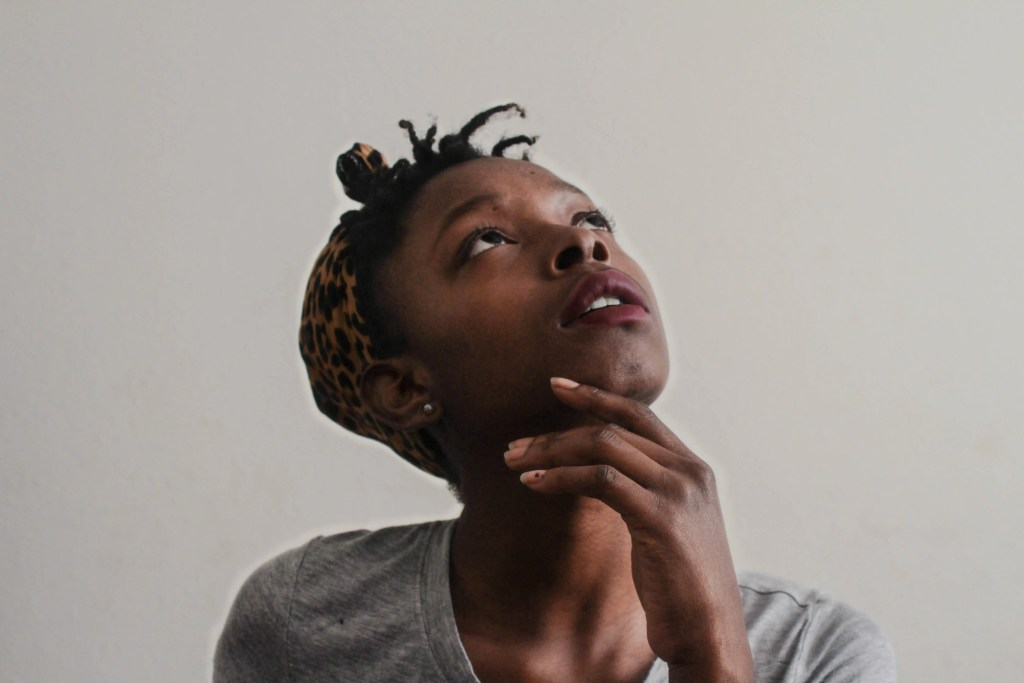 A black girl looking up and thinking